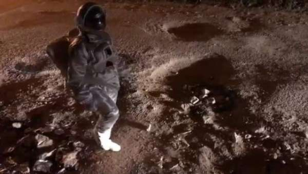 Artist Puts On Astronaut Costume To Highlight Crater-Size Road Potholes